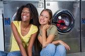 Fotografia amici di sesso femminile seduto insieme alla lavanderia