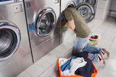 Fotografia uomo alla ricerca di vestiti allinterno della lavatrice