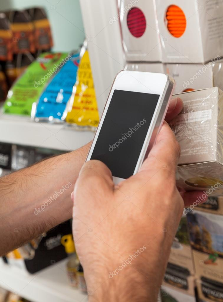 Man's Hand With Smart Phone Scanning Product