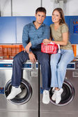 Fotografia coppia seduta su lavatrici