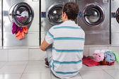 Fotografia uomo seduto di fronte a lavatrici