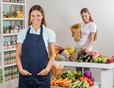Saleswoman With Female Customer Shopping At Supermarket