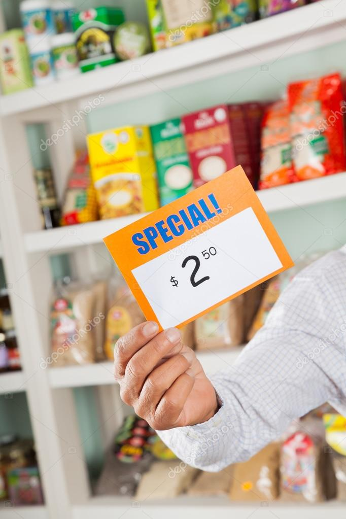 Male Owner Holding Discount Sign In Supermarket