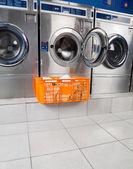 Fotografia cesto di vestiti davanti alla lavatrice