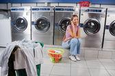 Fotografia bella donna con cellulare alla lavanderia