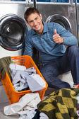 Fotografia pollice gesticolare uomo fino alla lavanderia