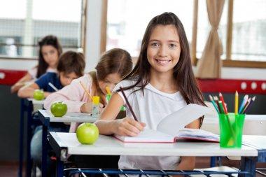 Schoolgirl Writing In Book At Classroom