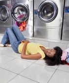 Fotografia donna che dorme sul pavimento a lavanderia