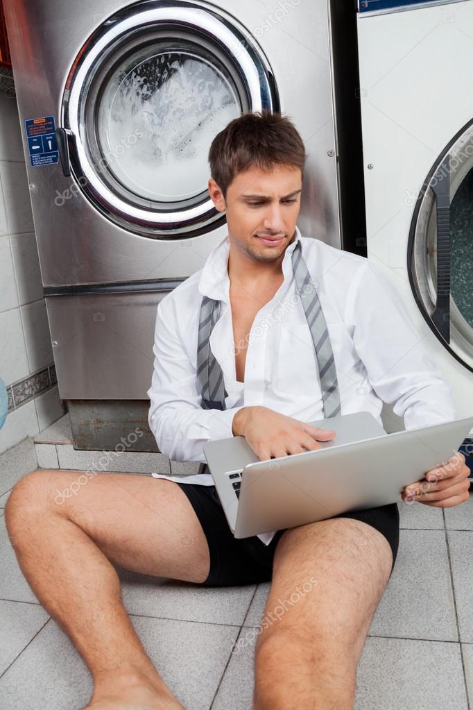 Businessman Using Laptop In Laundromat