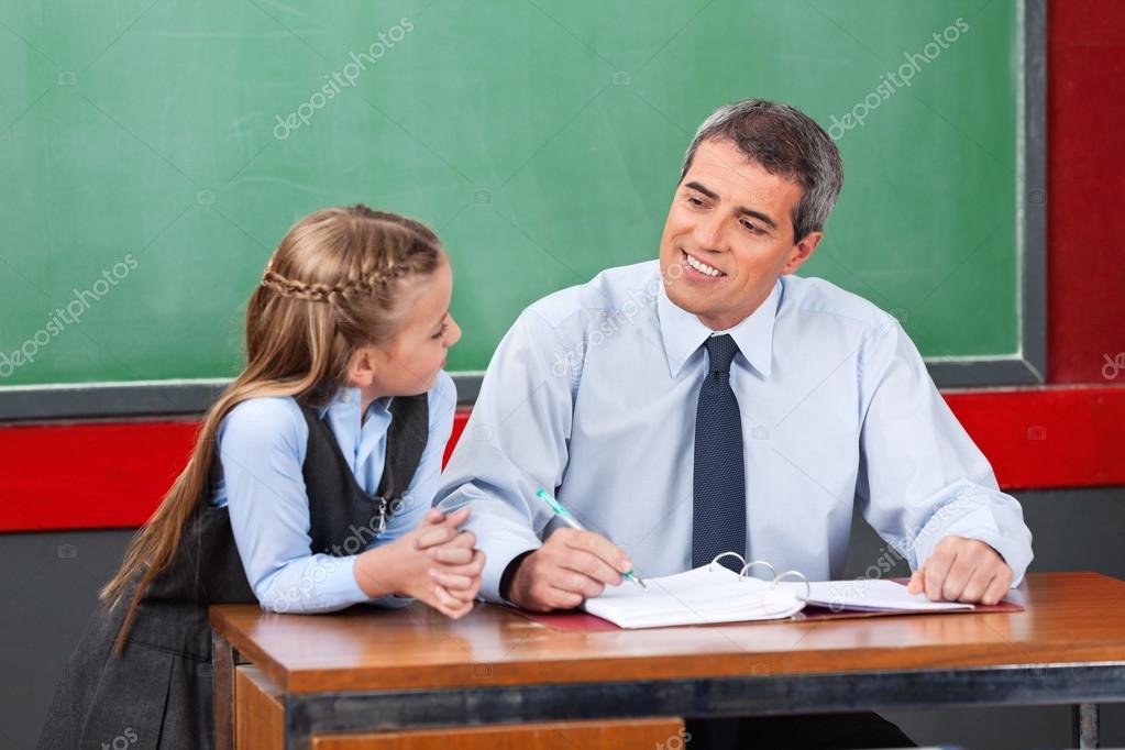 Male Teacher Looking At Schoolgirl In Classroom Stock Photo