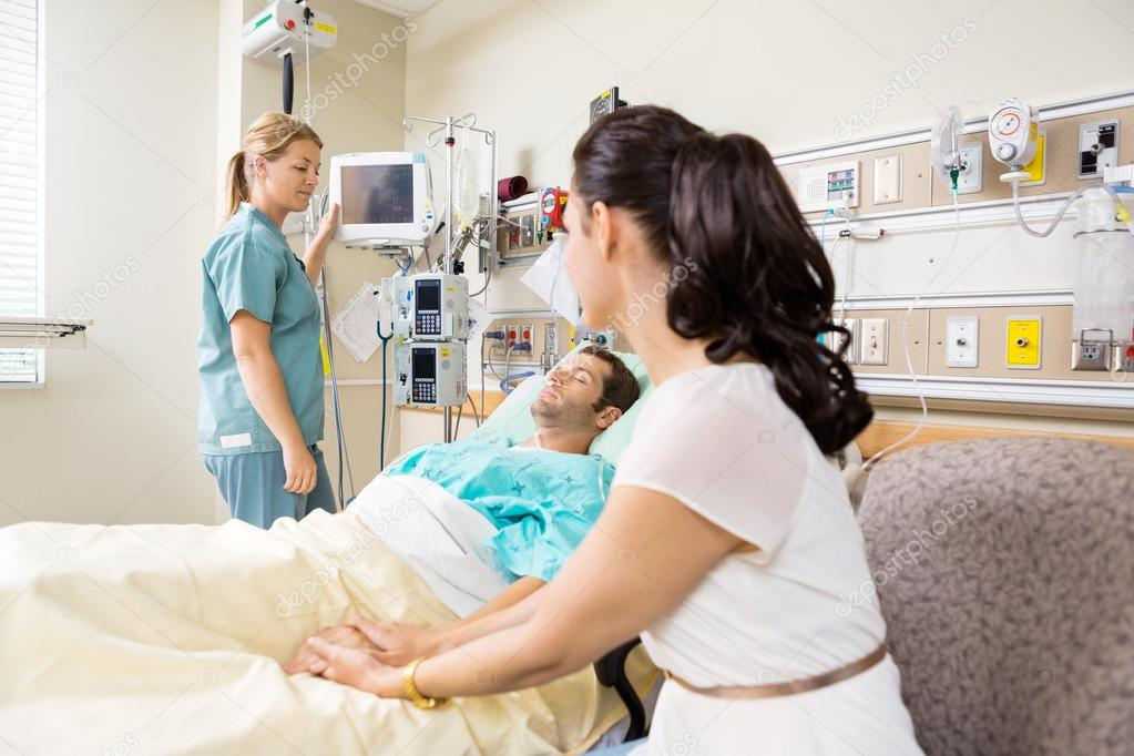 Woman Holding Patient's Hand In Hospital