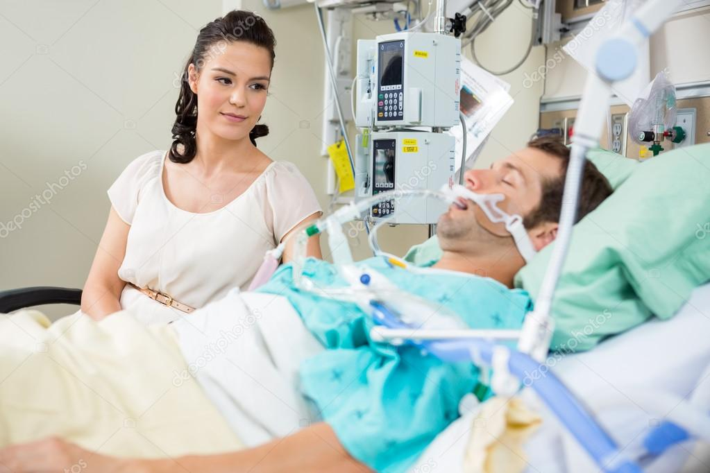 Woman Looking At Patient Resting On Bed
