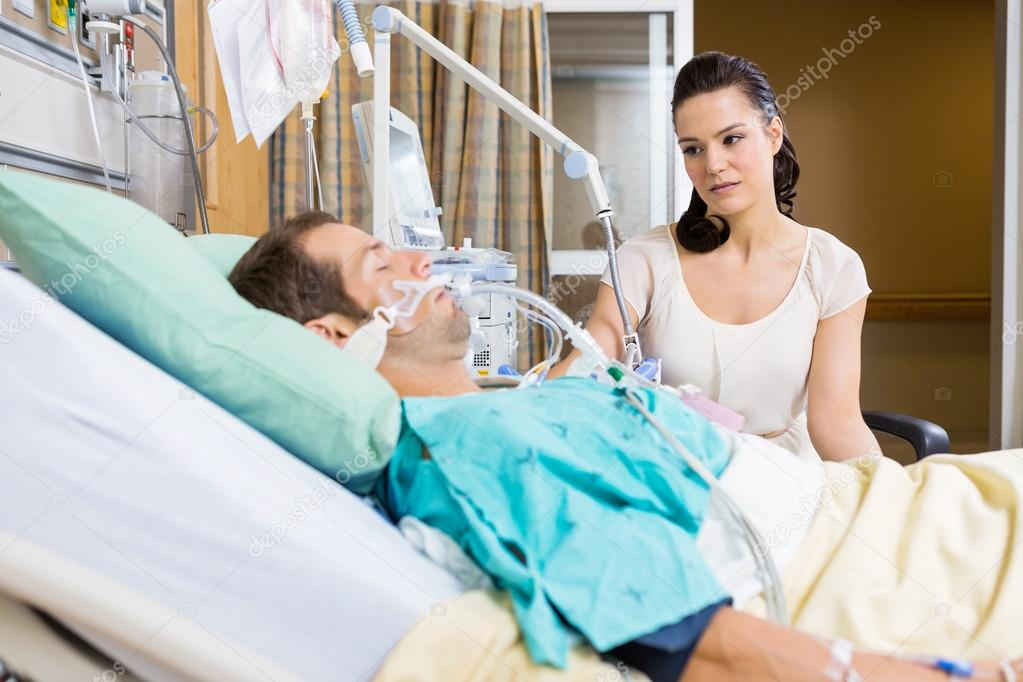 Woman Looking At Critical Patient Lying On Bed