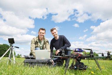 Men Using Laptop Next To UAV