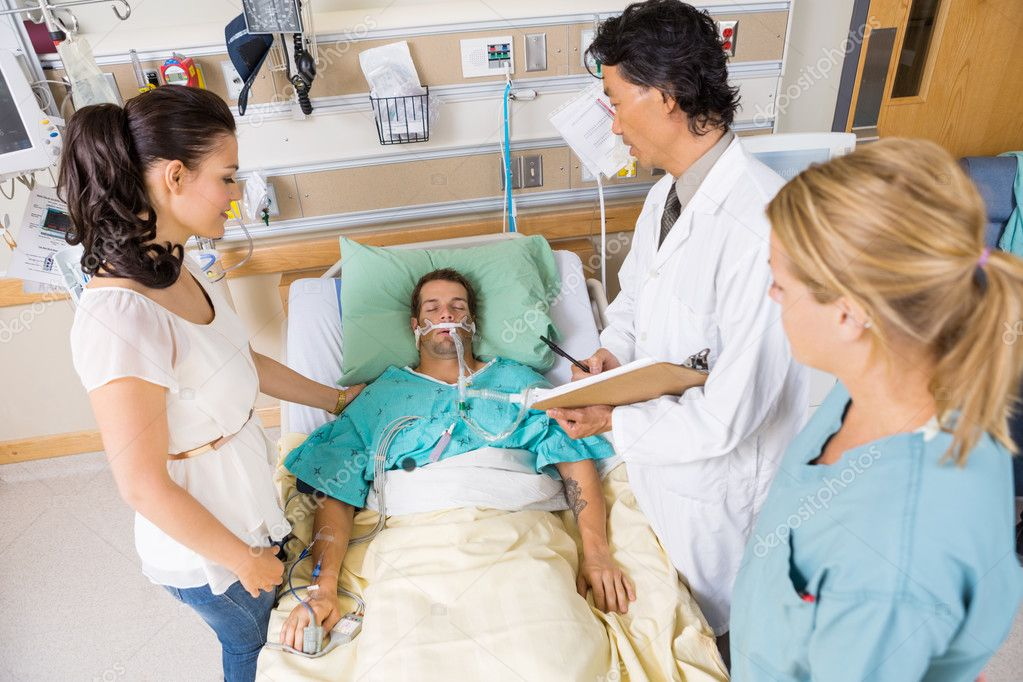 Doctor And Nurse With Woman Looking At Critical Patient