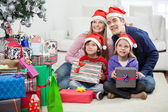 rodina v santa čepice sedí vánoční dárky