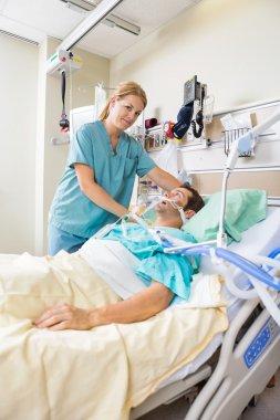 Nurse Adjusting Patient's Pillow In Hospital