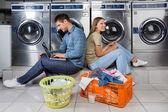 Fotografia coppia in lavanderia con computer portatile e auricolari