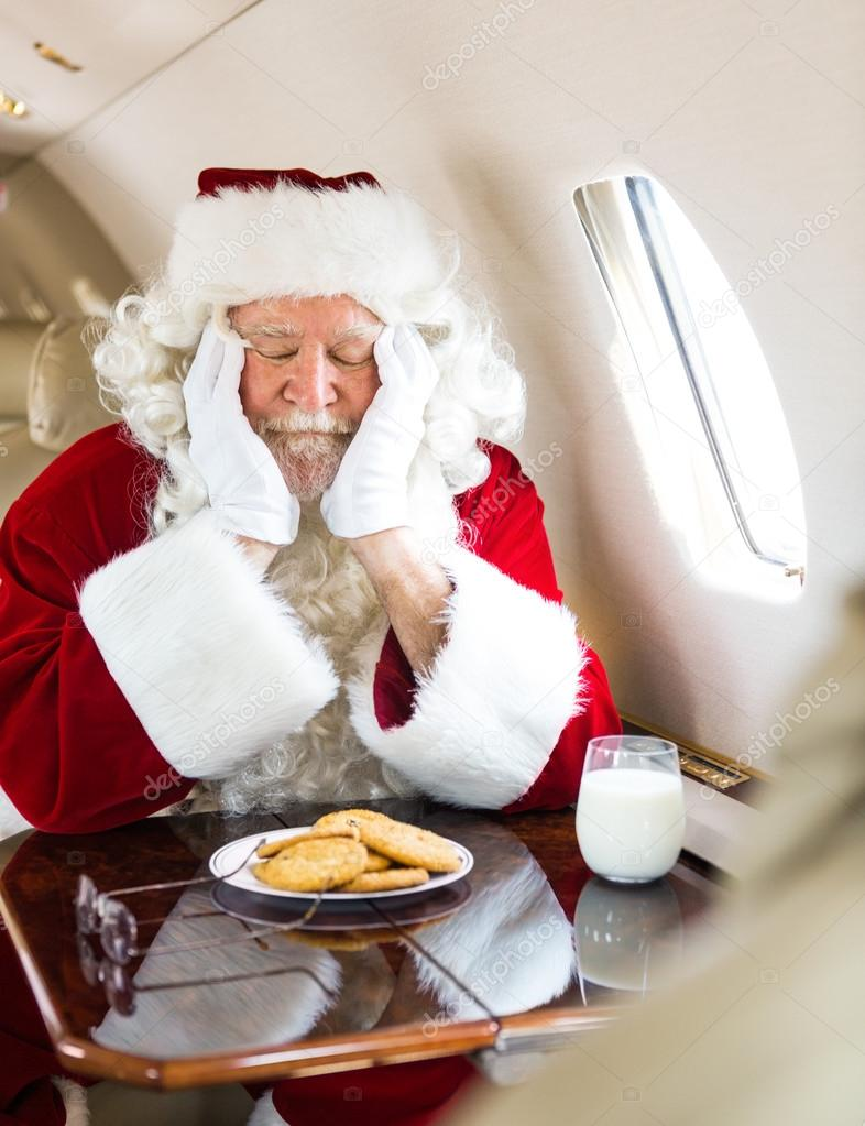 Santa With Cookies And Milk Sleeping In Private Jet Stock Photo