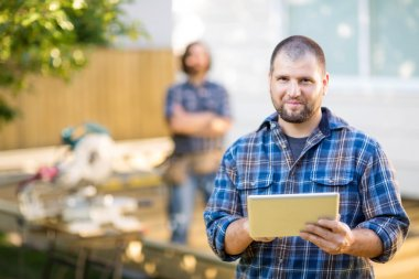 Manual Worker Holding Digital Tablet With Coworker Standing In B