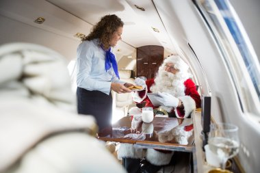 Airhostess Serving Cookies To Santa In Private Jet