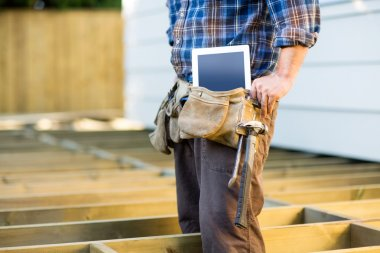 Midsection of construction worker with tablet computer and hammer in toolbelt at site stock vector