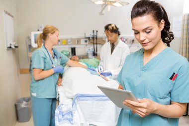 Nurse Using Digital Tablet While Doctor And Colleague Operating