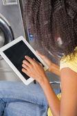 Fotografia giovane donna utilizzando una tavoletta digitale in lavanderia