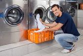 Fotografia giovane uomo mettere i vestiti in lavatrice