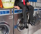 Fotografia uomo daffari seduto sulla lavatrice