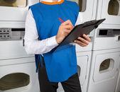 Fotografia supporto maschio scrivere Appunti in una lavanderia