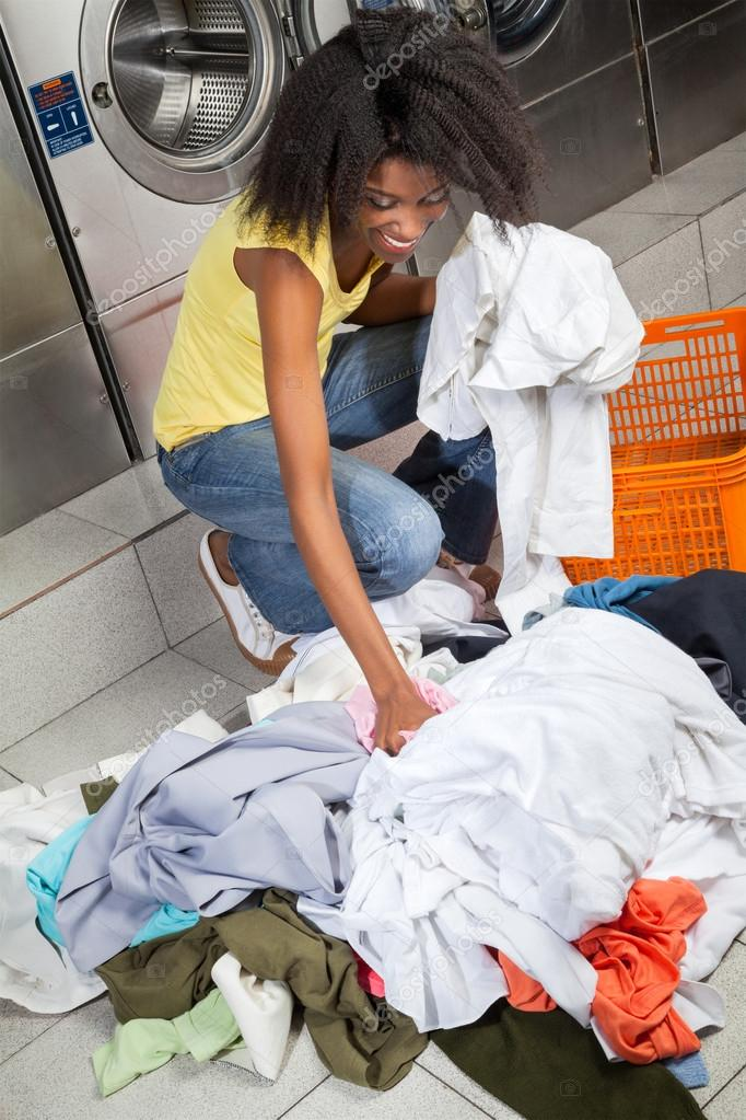 Woman Picking Dirty Clothes At Laundry