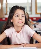Promyšlené školačka koukal sedíte za stolem