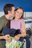 Fotografia uomo donna bacio sulla guancia alla lavanderia a gettoni