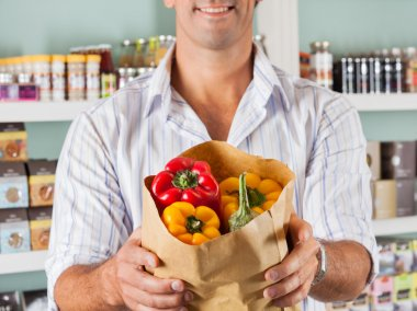 Male Customer Showing Bellpeppers In Paper Bag