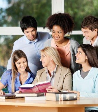 Female Teacher Explaining Students In Classroom