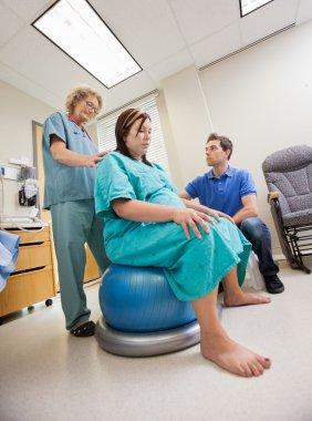 Nurse Assisting Pregnant Woman Sitting On Pilate Ball