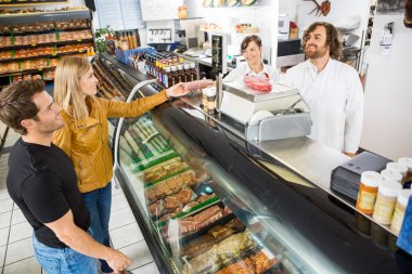 Couple Purchasing Meat From Salesman In Shop