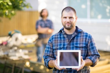Confident Carpenter Displaying Digital Tablet With Coworker In B