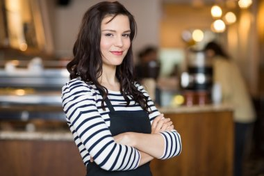 Pretty Waitress Standing Arms Crossed In Cafeteria
