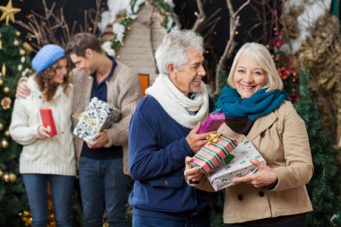 Senior Couple Holding Christmas Presents With Children In Backgr