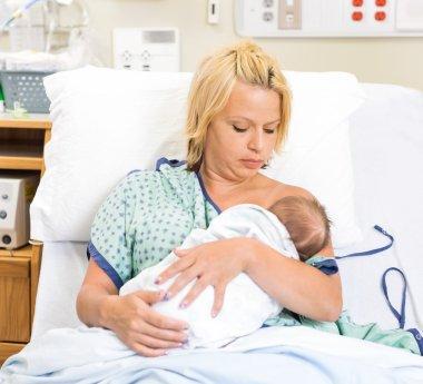 Woman Breast Feeding Newborn Babygirl In Hospital