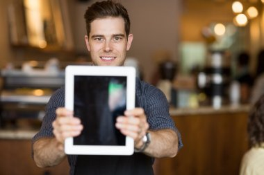 Cafe Owner Holding Digital Tablet In Restaurant