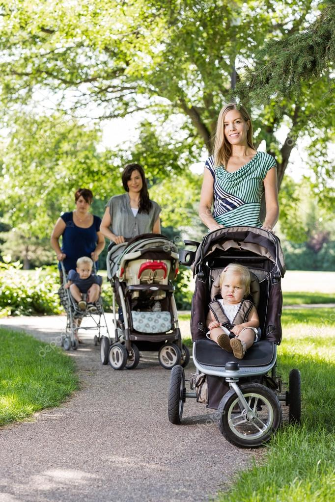 9219b331f64d Mothers Pushing Baby Strollers In Park — Stock Photo © SimpleFoto ...