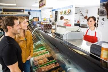 Saleswoman Attending Customers At Butcher's Shop