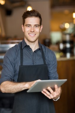 Happy Owner Holding Digital Tablet In Cafe