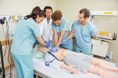 Medical Team Performing CPR On Dummy Patient