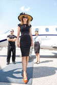 Fotografie Beautiful Woman With Bodyguard And Airhostess Against Private Pl