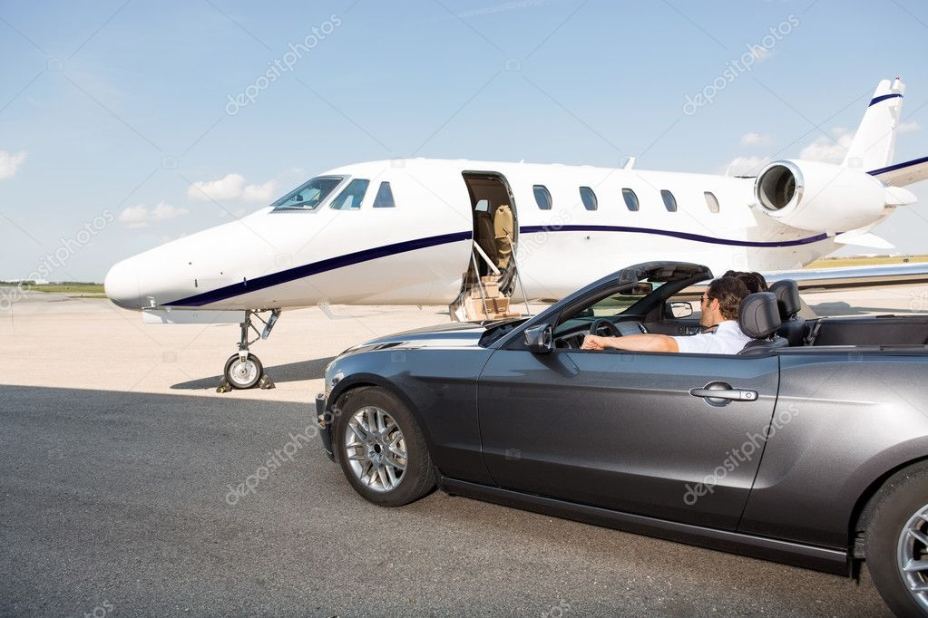 Pilot In Convertible Parked Against Private Jet