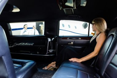 Woman In Limousine At Airport Terminal